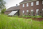 View from wild garden of raised beds with metal surrounds outside renovated, brick farmhouse