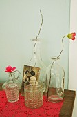 Poppies in various bottles and nostalgic photo on pink lace cloth