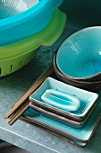 Chopsticks on stacked ceramic bowls with turquoise-glazed insides and brightly coloured plastic colanders on steel shelf in kitchen