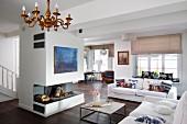 Offener Wohnraum mit weissen Sofas vor freistehendem, offenem Kamin mit modernem Bild in Blau