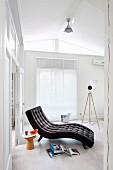 Anthrazitfarbene Liege mit Polsterknöpfen in puristischem, weißem Raum, Beistellhocker und Bücher am Boden