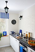 Modern kitchen counter with splashback tiled with white, structured strip tiles and accents of colour provided by blue accessories