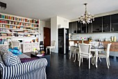 Everything in one room - eclectic dining area in front of modern kitchen counter, large bookcase and striped, country-house sofa