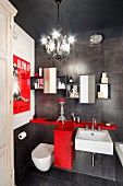 Vintage bathroom with charcoal tiles, red storage cabinet, film poster and chandelier