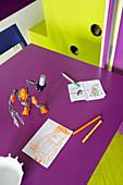Kinderzeichnungen und Spielzeugfigur auf der violetter Tischplatte, angrenzendes Einbaumöbel und Boden in komplementärem Lindgrün