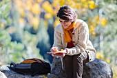 Frau sitzt mit Buch & Rucksack auf Felsvorsprung in herbstlicher Landschaft