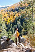 Woman wearing hiking gear standing with arm outstretched on rock ledge in autumnal mountain landscape
