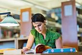 Studentin sitzt lernend über Bücher gebeugt in Bibliothek