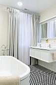 Bodenlange Vorhänge und schwarz-weisser Mosaikboden in elegantem Badezimmer