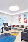 Brightly coloured scatter cushions on grey sofa and armchairs below pop-art-style pictures and round colourful rugs in front of fireplace