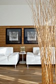 White sofas below black and white artistic photos on modern, half-height wood panelling behind partitions made from bundled brushwood
