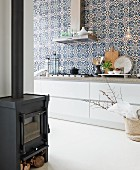 Blue and white Moroccan wall tiles above modern, elegant kitchen counter with wide drawers; wood-burning stove in foreground