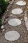 Runde Steinplatten auf gekiestem Gartenweg