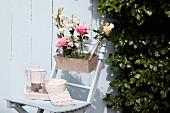 Blumenkasten mit verschiedenen Blumen in Flaschen auf Gartenstuhl vor weisser Holzwand