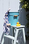 Blue metal bucket, bar of soap, cloth and yellow rubber duck on white wooden step ladder