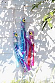 Hand-crafted, colourful crepe paper streamers hanging on white wooden facade