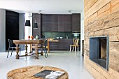 Fireplace in rustic wooden wall; dining area with antique table and modern, charcoal grey kitchen counter in background