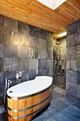 Designerbad mit Wanne im modernen Fass-Design und grauen Fliesen, offene Dusche im Hintergrund