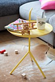 Wooden toys on yellow metal table on animal-skin rug
