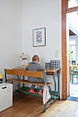 Little girl sitting on old school bench and desk combination next to open doorway