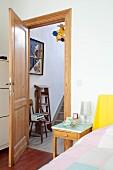 Ausschnitt eines Schlafzimmers, Nachttisch neben Bett und offener Zimmertür aus Holz mit Blick ins Treppenhaus