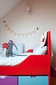 Ausschnitt eines Bettes, rot lackierter Rahmen und teilweise sichtbare farbige Schubladen