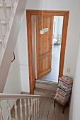 Blick von oben auf offene Badezimmertür im Treppenhaus, seitlich in Ecke Zeitschriftenstapel auf Hocker