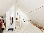 Attic dressing area with white-painted wooden floor, dormer window and mirror