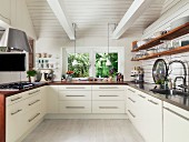 White, modern, fitted kitchen in renovated country house with crockery on wooden shelves, worksurfaces and exposed, white roof beams