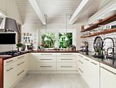 Moderne weiße Einbauküche in renoviertem Landhaus mit Holz-Geschirrboards, Küchentheke und sichtbaren weißen Balken