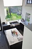 Vogelperspektive auf puristische Einbauküche mit freistehendem Arbeitsblock und integrierter Betonspüle vor Fenster