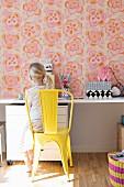 Mädchen auf gelb lackiertem Metallstuhl vor Schreibtisch, an Wand Retro Blumentapete