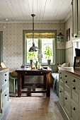 Rustic kitchen with pale grey cupboards and solid-wood dining table in background