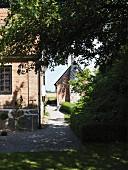 Umlaufender gekiester Gartenweg am Wohnhaus mit Ziegelfassade