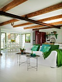 Delicate tray tables in front of sofa with white loose cover and scatter cushions in various shades of green in open-plan interior with dining area in background