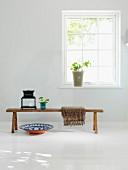 Rustikale Holzbank mit Laterne und Keramikschale auf weißem Holzdielenboden vor Sprossenfenster