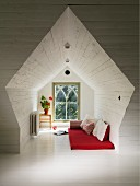 Wood-clad niche in converted attic; red futon and cushions on white-painted wooden floor