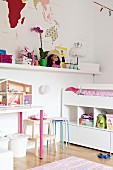 White loft bed with shelves below, toys on shelf and dolls' house on table in girl's bedroom