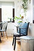 Zinc bin next to black, wooden armchair in dining room