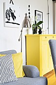 Sofa with one patterned and one yellow scatter cushion and yellow-painted cabinet against wall