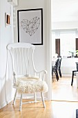 White wooden chair with high backrest and fur cushion in corner; view into dining room through open door to one side