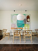 Dining set with pale wooden classic chairs on rug below white designer pendant lamp in front of modern artwork on wall