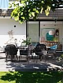 Grey-brown cane chairs around table on wooden terrace outside contemporary house