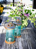 Two vintage lanterns and vase of lilac on wooden table