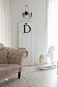 Antikes Sofa in Beige, ausgebautes Türblatt und weisses Schaukelpferd in nostalgischem Wohnraum