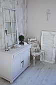 Old window frame on top of white-painted cabinet next to kitchen chair and window shutter in shabby-chic interior