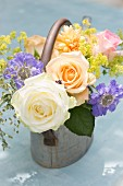 Romantic posy of roses and scabious in metal watering can