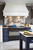 Gas cooker flanked by blue-painted drawer units below masonry mantel hood