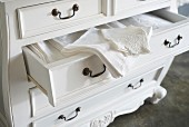 Elegant table linen in open drawer of white Baroque chest of drawers