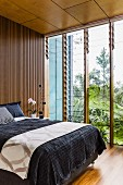Double bed with black bedspread against wall with slatted wooden cladding next to glass wall with adjustable glass louvres